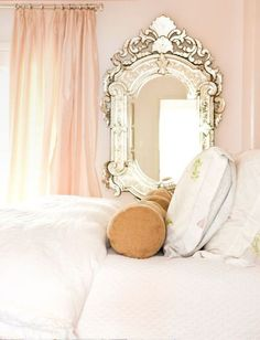 fabulous Venetian mirror, petal pink draperies, blush pink walls, and gold roll pillows.   Devastatingly romantic!
