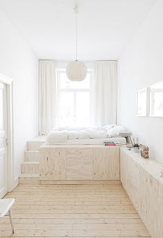 White bedroom with plywood platform bed and cabinets along wall and pine floors in Wiesbaden Apartment by Studio Oink | Remodelista