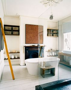i-peach-feng-shui:    (via lookmom)  A bathtub next to a fireplace is like ice cubes on a stove- its definitely not idea ( kinda like my stove beside my refrigerator- which I have no control over!) So, what does one do? ADD WOOD. The wood floor ( if it were not painted) and the wood accoutrement help this room out definitively to create balance…