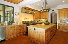 spanish style kitchen: love the wood work, just needs more color accents!