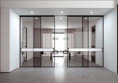 Porta scorrevole a quattro ante con binario incassato nel soffitto. Doppio vetro neutro con fascia centrale in gres porcellanato oxide bianco