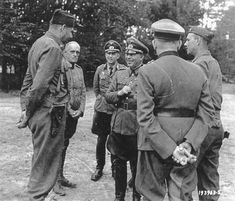 Lt. Col. Bertram Kalisch, left, Forest Milles, LI, NY, and Lt. Col. J. K. French, right, Fairfax County, VA, discuss terms of surrender with German Maj. Gen. Erich Elster and his staff at the River Loire.  Although the General is surrendering 20,000 troops, he seems cheerful.  Romorantin, France, 09/15/1944.