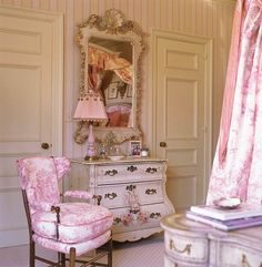 Pretty details like fringe on the lampshade and a gilded mirror frame make the pink toile feel ultra-feminine in this bedroom by Charles Faudree- Traditional Home®