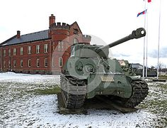 Sherman tank from World War ll in front of an old armory building.