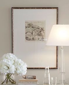 Flowers, books, lamp and artwork all in a simple white palette with gold makes a very striking and pleasing vignette.