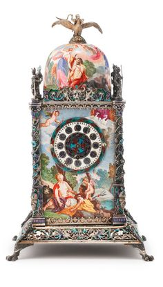 *AN AUSTRIAN SILVER AND ENAMEL TOWER CLOCK, VIENNA, LATE 19TH CENTURY the square base raised on paw feet, tower-form with openwork scrolling foliate borders, each side set with an enameled plaque of classical figures, the front set with an enameled clock dial, the columns at the corners surmounted by knight figures, the enameled domed top with a finial of a winged man riding a bird apparently unmarked height 8 1/8 in. 20.6cm