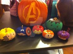 """This year for Halloween, I decided to go all out and make Avengers pumpkins! From left to right: Thor, Captain America, Iron Man, Black Widow, The Hulk, and Hawkeye. The big ol' Avengers """"A"""" is the..."""