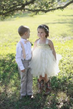 Rustic, outdoor wedding with peach/ coral, mint color scheme, boutonniere with greenery, ring bearer in bow ties and suspenders, flower girl in country princess tulle dress and boots | Christine Gosch