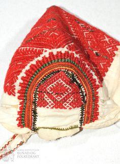 """Spebarnslue, eller """"dregilhuve"""" sydd av bomullslerret med smøygsaum av ullgarn i flere farger, rødt, grønt og svart på """"blesi"""", bakstykket og dregilen. De broderte feltene er på lin. Bakstykket har smøygsaum i kross og kringle mønster. Smøyg også på blesi, med ei kringle midt fremme. Kun håndsøm. Scandinavian, Winter Hats, Embroidery, Blanket, Crochet, Norway, Vintage, Baby, Needlepoint"""
