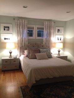 Window treatments master bedroom. Oriental chalk paint Paris grey night stands. Velvet headboard. Curtains behind headboard. Transom window above bed. Healing aloe Benjamin Moore paint. White bedding. White frame with Matte black and white photos.