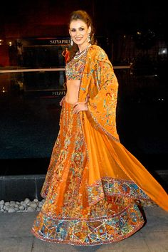 Orange dupion lehenga beautifully blended with modern kaleidoscopic and traditional ornamental patterns. Orange georgette dupatta compliments the ensemble perfectly with ornamental jaal in center and heavily embroidered palla.