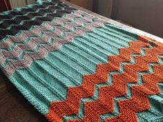 """Danielle offers a pattern for """"the Walt"""" afghan, which features raised stripes of garter Chevron that give baby a nice texture to play with. Select a neutral with lots of bold stripes or choose a bright background to put neutral and colorful stripes over. Pattern at click"""