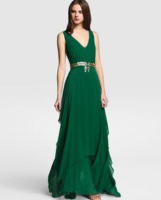Vestido largo con bajo desigual en color verde. Tiene adorno de strass en la cintura, sin mangas y con escote de pico.