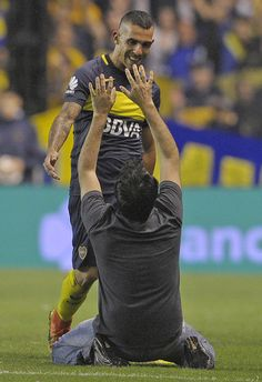 An unidentified fan cheers Boca Juniors' forward Carlos Tevez (back) as he leaves the field during their Argentina First Division football match against Colon at La Bombonera stadium, in Buenos Aires, on December 18, 2016. / AFP / ALEJANDRO PAGNI