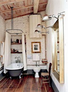 Rustic clawfoot bathtub in bathroom with exposed ceiling beams