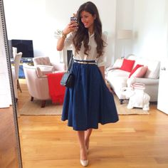 Midi A line navy skirt w classic button white top, thin white belt, white pumps.