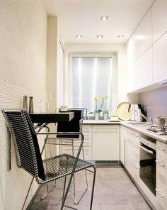 Przykład 1. W tej nieustawnej kuchni zmieścił się tylko niewielki kącik śniadaniowy.  Opuszczany blat został przymocowany do ściany w takim miejscu, by nawet po podniesieniu nie przeszkadzał w pracy i nie utrudniał poruszania się po pomieszczeniu.