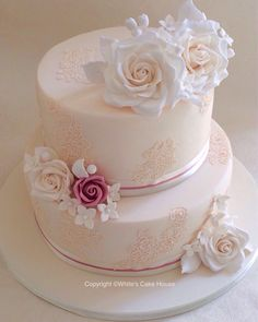 A pretty two tier wedding cake with lace and large sugar roses