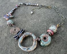 https://flic.kr/p/cJLRg7 | Washed Out to Sea | raku round beads and ammonite by Suburban Girl Studio, polymer donut and bronze lichen donut by me.  Collab piece for Bead Fest Philly.  I loved the blues of Diana's beads, and wanted to compliment that washed look.  I was going to use darker colors with the piece, but pulled out this donut and loved the washed out look the colors all had, like they were very old...which went well with the fossil ammonite.