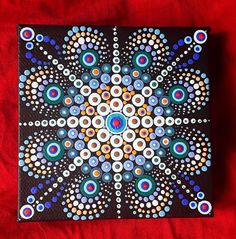 Daystar Mandala. A vibrant blue and orange starburst Mandala. Acrylic on canvas with fluorescent orange centre 4x4 inches