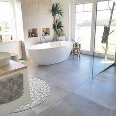 Grote Scandinavische badkamer inrichting inspiratie met beton look en vrijstaand bad. Mooi detail is de grote plant in deze badkamer. Daarnaast een grote inloopdouche rechts. Grote tegels en zwevend meubel maken het af. Wat een prachtige inspiratie! Ook zo'n mooie Scandinavische badkamer, groot of klein? Klik op de foto en laat een offerte voor een complete badkamer maken via Skype of Facetime!
