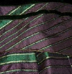 Ca. 1860 violet striped silk dress with large bell sleeves. Detail of sleeve cap or jockey over pleated lower sleeve, showing tiny piping at edge of jockey and black velvet ribbon trim.