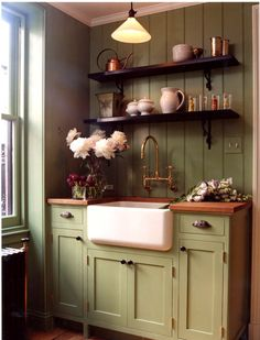I love the contrast of the dark shelving, the wood counter top and the green cabinets with the ivory farm sink....beautiful combination!!