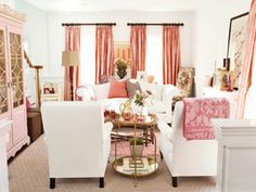 "Pink and White Find A Balance--This thoughtfully composed yet comfortable design scheme of ""pink-white-pink"" establishes an orderly decorating plan in the living room. At its heart, the central cluster of upholstery  maintains a peaceful balance. White is the gentle, tempering force, working its magic on custom-smocked salmon drapes, a whimsical cotton-candy flokati rug, and an array of patterned textiles."