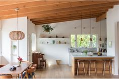 Light-filled interior with open plan, counter, pendant lights, open shelving, wood floors and wood ceiling.