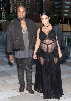 Kim Kardashian wears a full length black dress with sheer panels and lace.