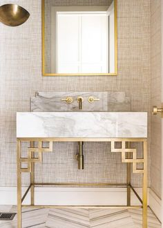 Fixed on a wall covered in tan textured wallpaper a gold sconce lights a gold beveled mirror located above a brass faucet mounted on a marble backsplash accenting a thick marble countertop on a brass base placed on marble herringbone floor tiles in this well appointed gold and tan powder room.