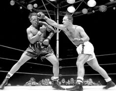 Rocky Marciano lunges with his right as Archie Moore braces for the impending blow on Sept. 21, 1955.