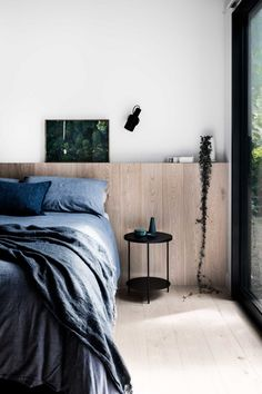 Home Decor Minimalist Built-in oak plank ledge takes the place of a traditional headboard in this minimal bedroom with blue bed linen and black metal furniture