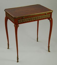 "A fine table à écrire in kingwood veneer over oak attributed to the ebeniste Pierre Pioniez, the canted rectangular top with a gilt-bronze edging and inlaid with marquetry of a village scene within a oval flanked by flowers, with a replaced pull-out writing slide with a leather inset and a full-width frieze drawer, the frieze mounted with gilt-bronze interlocking rings all around. | Circa. 1770-1785. | H 25 ¼"", W 23 ½"", D 16"" 