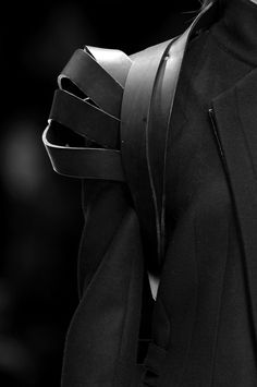 Leather shoulder harness detail - sculptural fashion design features; material contrasts