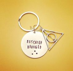 Mischief Managed Deathly Hallows Key Chain - Harry Potter Inspired Geekery This 2 silver key chain is hand stamped with the words, MISCHIEF MANAGED. A silver tone deathly hallows charm hands beside it. Neat gift for a fan or a nice addition to your Potter collection! Thank you for looking!