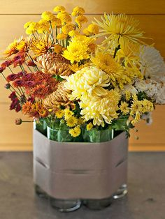For an arrangement with big impact, arrange flowers in tall cylinder vases and place the vases together. Warp the grouping with wide ribbon ...