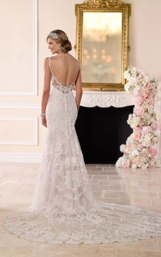 Antique-inspired romantic lace detailing adorns this modified fit-and-flare wedding gown from Stella York.
