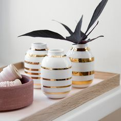 The simple and balanced shape of the delicate Omaggio vases is contrasted by the strong and graphic gold stripes.
