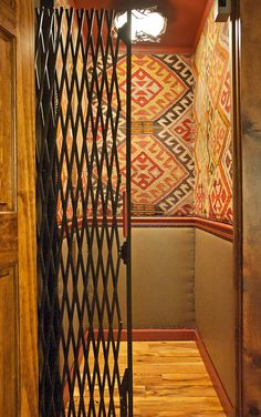 Elevator cab upholstered above chairrail in antique kilim rug