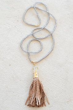 Tassels are so IN...especially when featured on a necklace as beautiful as this one! Our 'Kathryn' necklace features a grey iridescent beaded chain. Lobster clasp closure. Brown snake printed suede ta