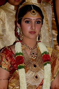 """This is what a traditional Indian bride looks like. She is supposed to wear a silk saree with a reddish hue-- like red, burgundy, maroon, copper or pink. Red represents honor, love and prosperity. A flower garland goes over her dress. And then lots of gold jewelry. A """"mang-tikka"""" (upper forehead jewelry) hangs down from the part in her hair! Dangling earrings, multiple necklaces and a """"bindi""""between her eyebrows. The hair must be in an up-do, as it's considered immodest if you wear it down."""