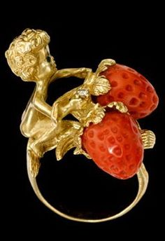 Whimsical 14 karat yellow gold ring with coral accent   1950s   Ruser inspired lady's ring of young boy sitting in a strawberry patch with two coral strawberries, carved.