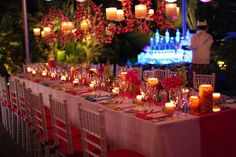 Tropical wedding. White table setting with fresh orchids in purple and magenta, accented with Damask pillars in fuschia and ornage.