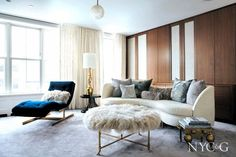 Chic and glamorous living room with dark blue lounge chair, white sofa, and furry stool