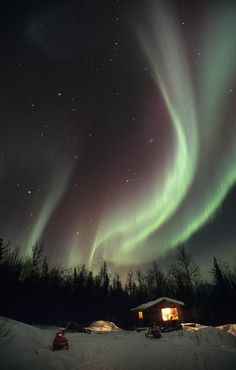 The aurora borealis, or northern lights, dance in the night sky above a cabin in Alaska's interior near Fairbanks.  COPYRIGHT:M. Scott Moon	 SIZE:3442x5400 / 53.2MB