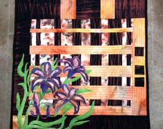 I used raw edge applique to apply the clematis and leaves to the background of pieced shapes. This piece measures 22 tall by 23.5  wide. There are either tabs or corners on the back for hanging with a dowel (dowel is not provided).