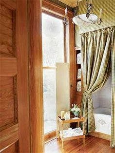 Gerrie Bremermann designed this charming bath.  Note the checkered shower curtain matches the upholstered walls and the solid shutter treatment at the window