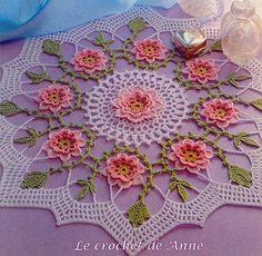 Me voici de nouveau pour vous présenter mon ouvrage , ce joli napperon aux fleurs roses en relief , bordées de feuilles vertes et d'une bordure blanche ! Je le trouve tout simplement magnifique ! Voici le modèle original , Sa grille au crochet n° 1,50...