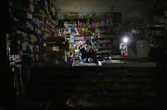 Superstorm sandy supplies: Park Choul waits behind the counter in his deli lit by flashlights